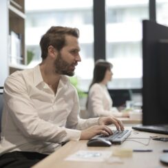 Thoughtful young manager typing on keyboard while working on computer in modern office