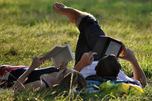 two people reading books at park - Paperback Book vs. Kindle eBook Readers