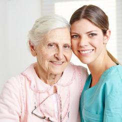 Smiling caregiver caregiving happy senior woman in nursing home