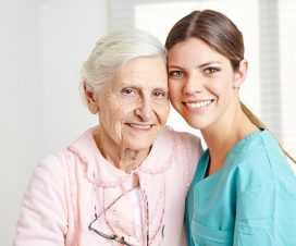 Smiling caregiver caregiving happy senior woman in nursing home