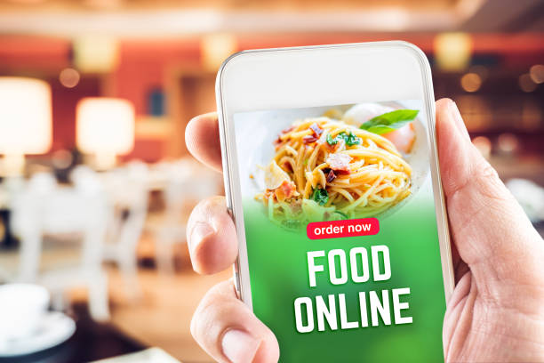 Close up hand holding mobile with order food online word on screen with blur restaurant bokeh light background, online marketing concept, online food delivery business
