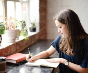 Young graduate Hannah Olinger writing thesis at home photo