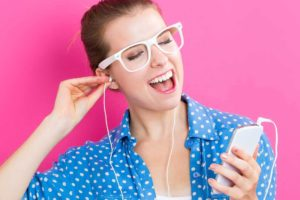Happy cheerful girl with earbuds enjoying music.