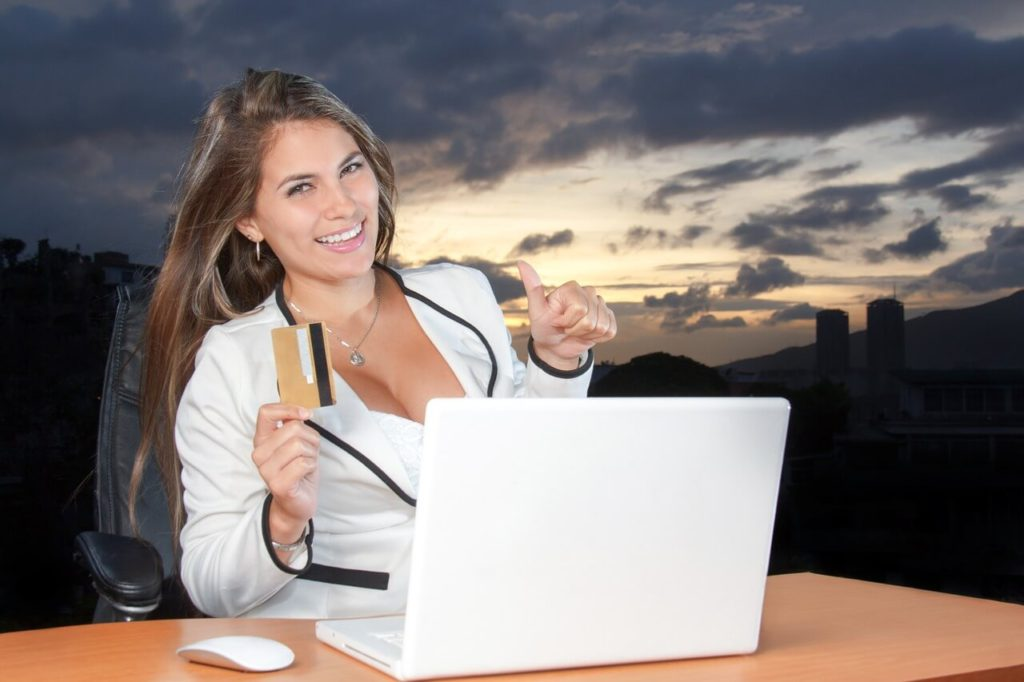 Young woman shopping online, holding prepaid card, paying on web via laptop computer, making secure online payment, purchasing goods in eCommerce store.