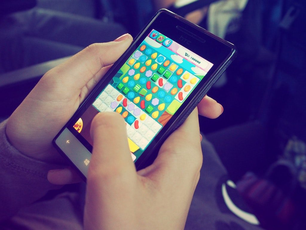 Person Playing Candy Crush Game on Smartphone