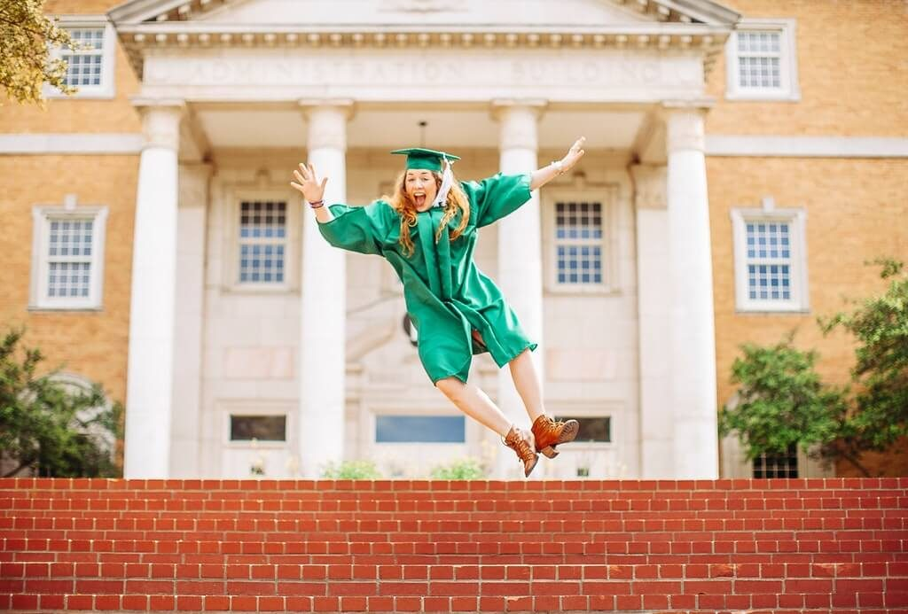 Woman jumping above stairs wearing graduation gown and a hat.