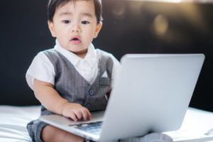 Asian tech-savvy baby in business concept use computer laptop