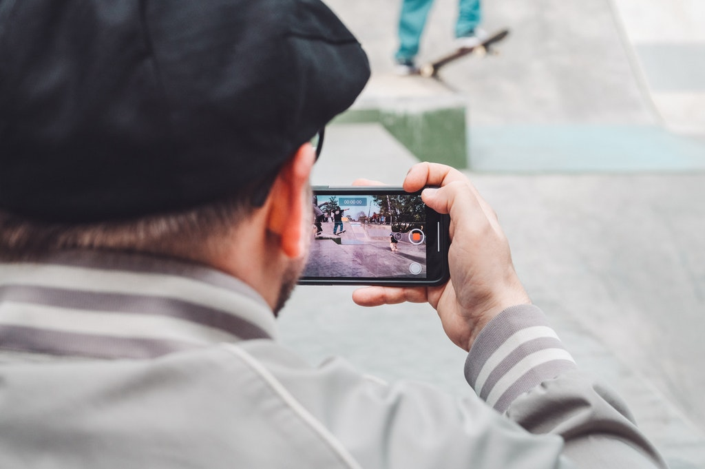Person Holding Mobile Phone Recording a Video. Smartphone Video Recording. Skateboarding. Videography. Technology.