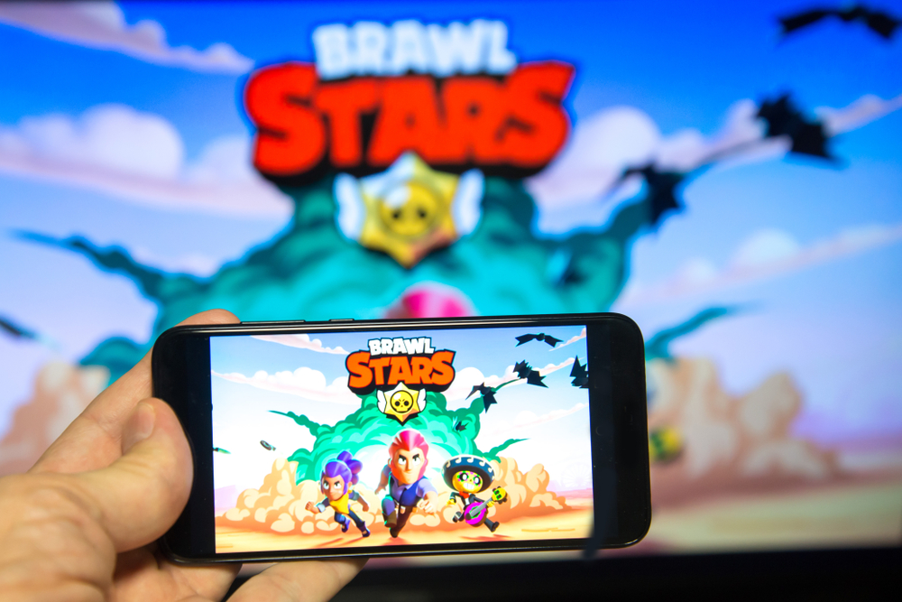 Hands holding a smartphone with BRAWL STARS game on screen background. Brawl Stars Mobile Game. Best Multiplayer Games for Android in 2020.