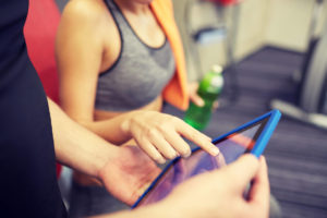 Personal Trainer and Gym Software. Close up of trainer hands with tablet PC in gym.