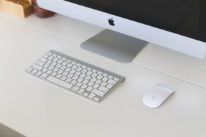 Apple Mac Computer, Keyboard on Desk. MacOS Catalina - Apple Desktop Operating System. Software by Apple.