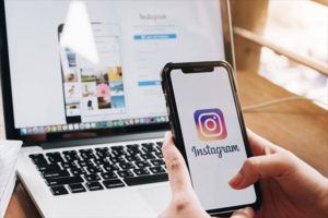 Boost Your Brand Awareness on Instagram. A woman holds Apple iPhone X with Instagram application on the screen. Instagram is a photo-sharing app for smartphones.