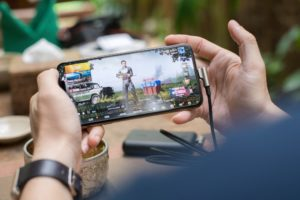 Mobile Gaming, Person Playing PUBG Game on Smartphone.