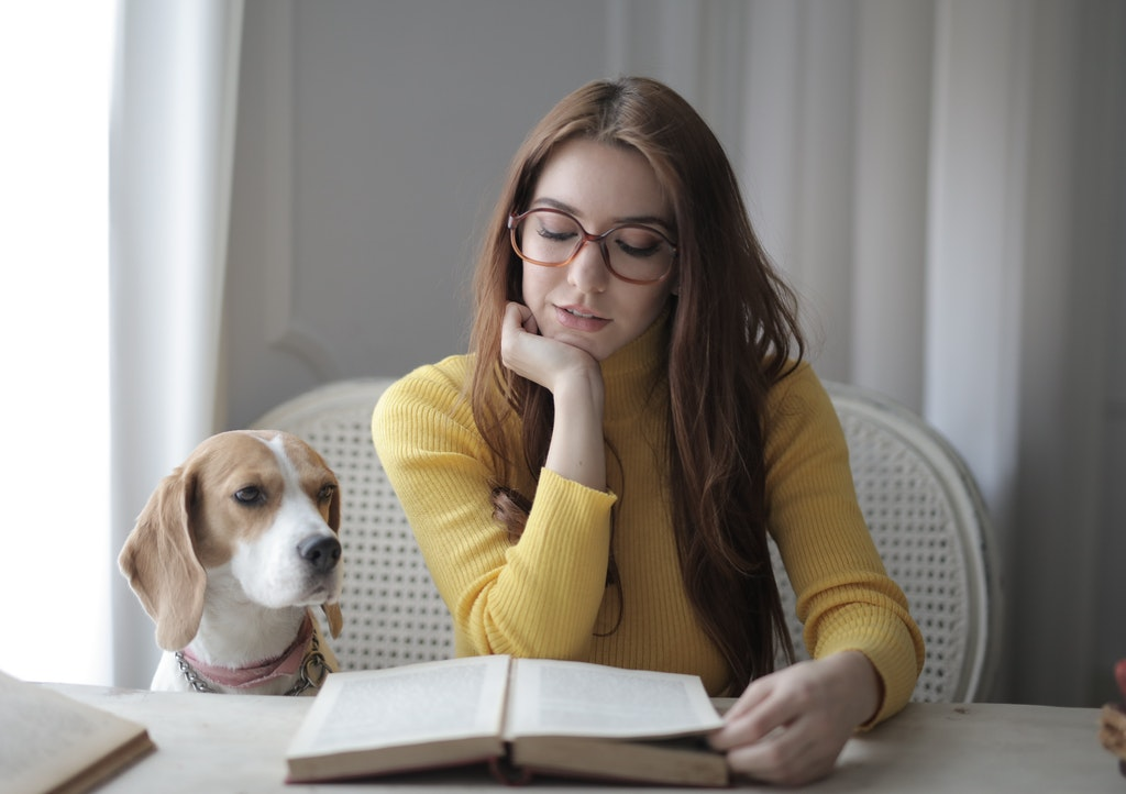 Woman Reading a Book and a Dog Sitting Next to Her. Education, Reading, Studying, Educational Support.