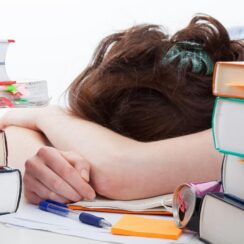 Tired college student falling asleep on books photo.