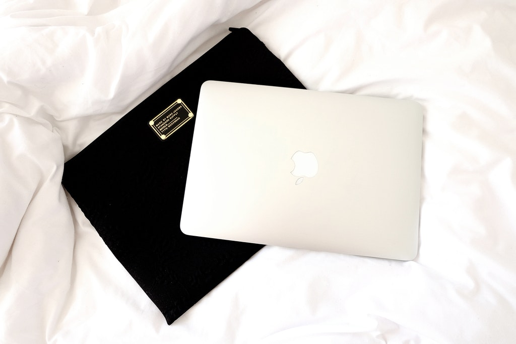 Silver Macbook on Marc Jacobs Black Laptop Case.