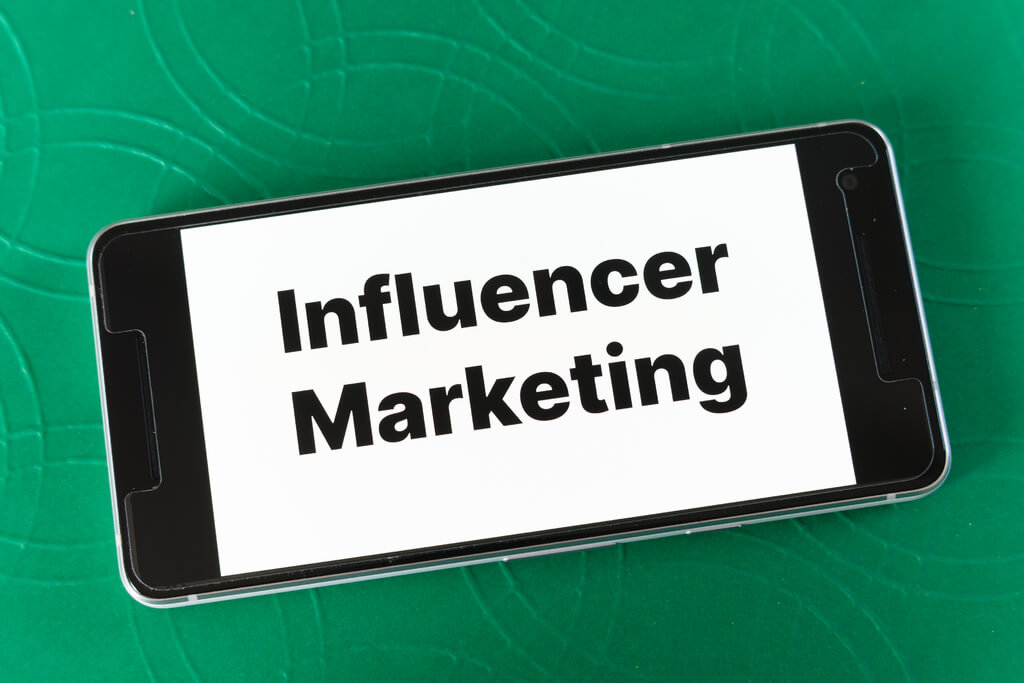 The Word Influencer Marketing on a Smartphone Screen.