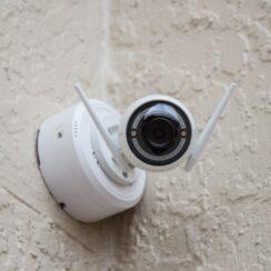 White Surveillance Camera Hanging on Wall Photo