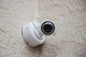 White Surveillance Camera Hanging on Wall Photo