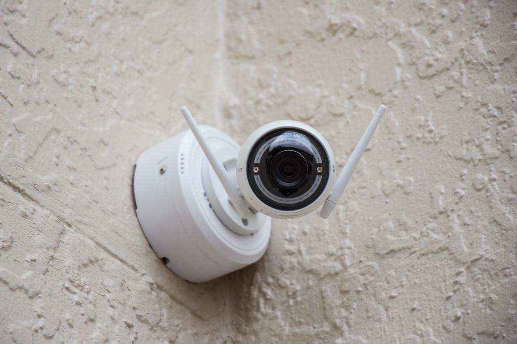 White Surveillance Camera Hanging on Wall Photo.