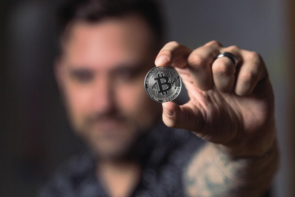 Bitcoin Trader or Person Holding Silver Bitcoin Coin.