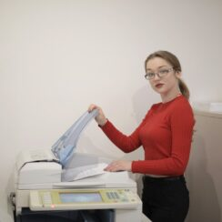 Female office worker using printer in workplace