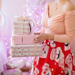 Woman Wearing Pink V-neck Long-sleeved Shirt and Red Skirt Holding Christmas Gifts