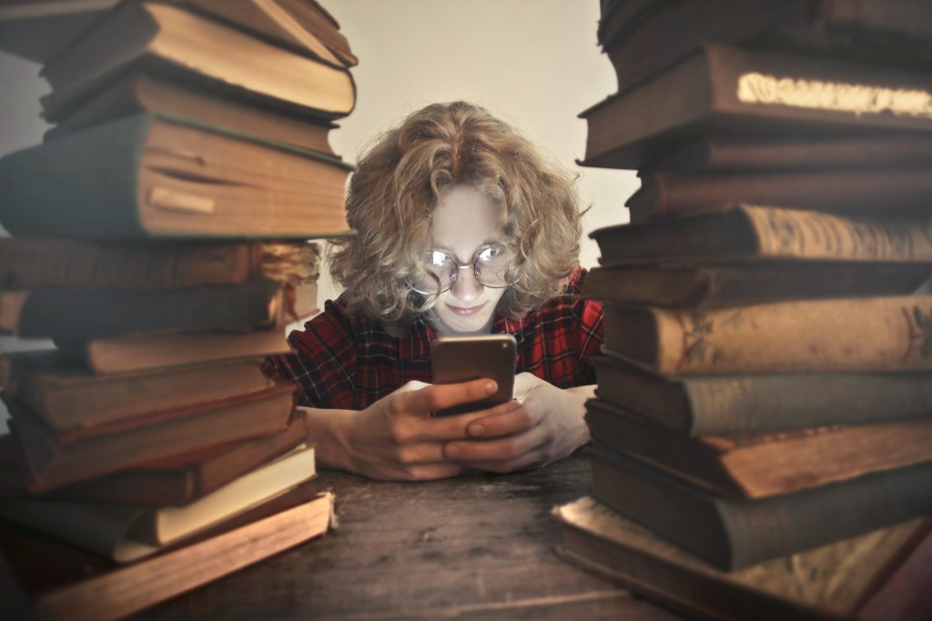 Student browsing smartphone at table with books