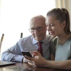 Young lady showing photos on smartphone to senior man