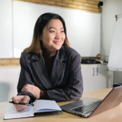 Charming Cheerful Woman Doing Content Moderation Using Laptop and Diary