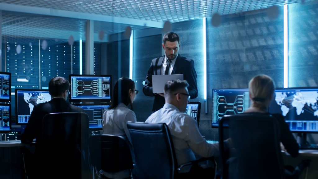 Professional IT Engineers Working in System Control Center Full of Monitors and Servers. Supervisor Holds Laptop and Holds a Briefing on Network Infrastructure Security