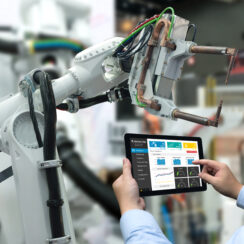 Engineer hand using tablet, heavy automation robot arm machine in smart factory industrial with tablet real time monitoring system application. Machine learning operations (MLOps)
