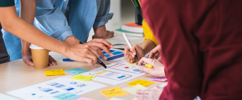 Close up ux developer and ui designer brainstorming about mobile app interface wireframe design on table with customer brief and color code at modern office.