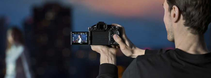Man holding Sony Alpha 7S III camera  recording a video.