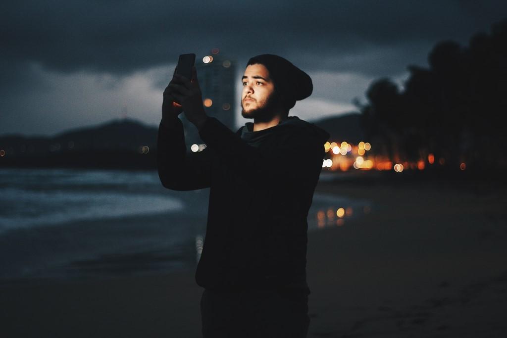 Man capturing Milky Way using smartphone on beach during dusk photo